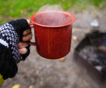 Gloved hand with a mug of something hot